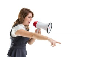 Young woman shouting into bullhorn as she points over white background